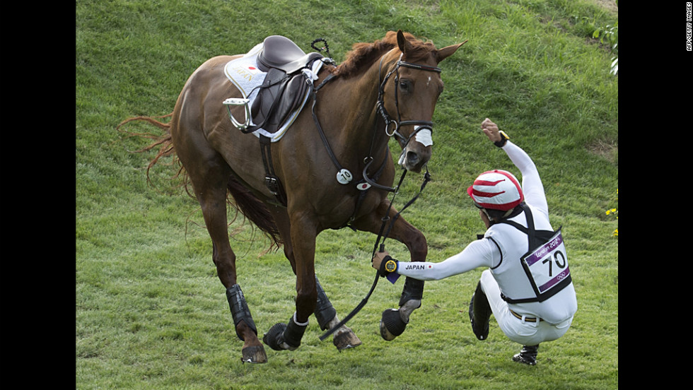 Japan's Yoshiaki Oiwa falls off his horse as he competes in the cross country competition on Monday.