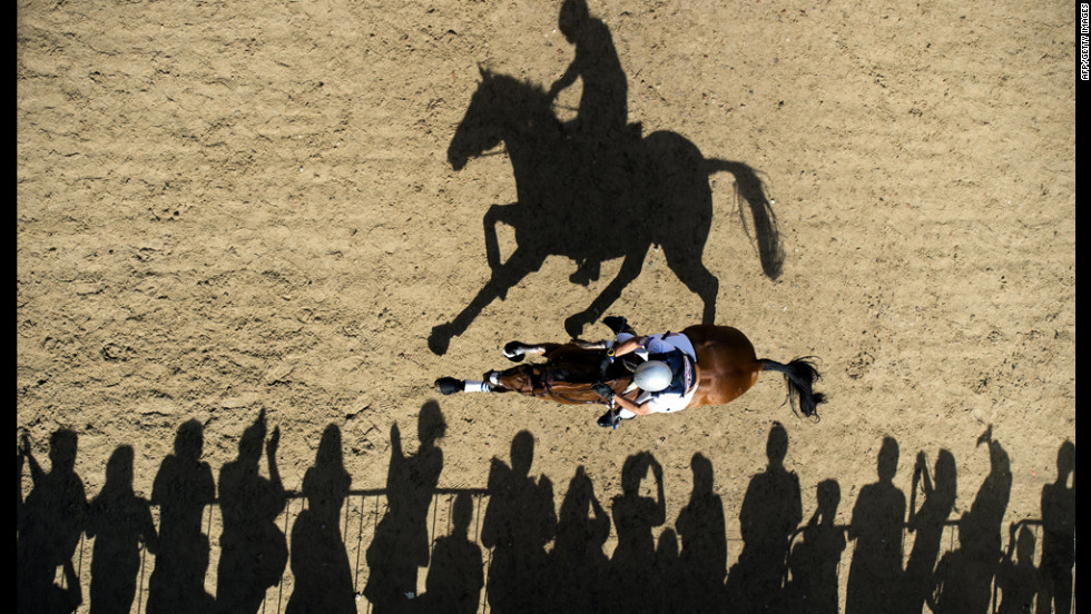 Atop Twizzel, William Coleman of the U.S. rides past spectators as he competes in the cross country equestrian event on Monday.