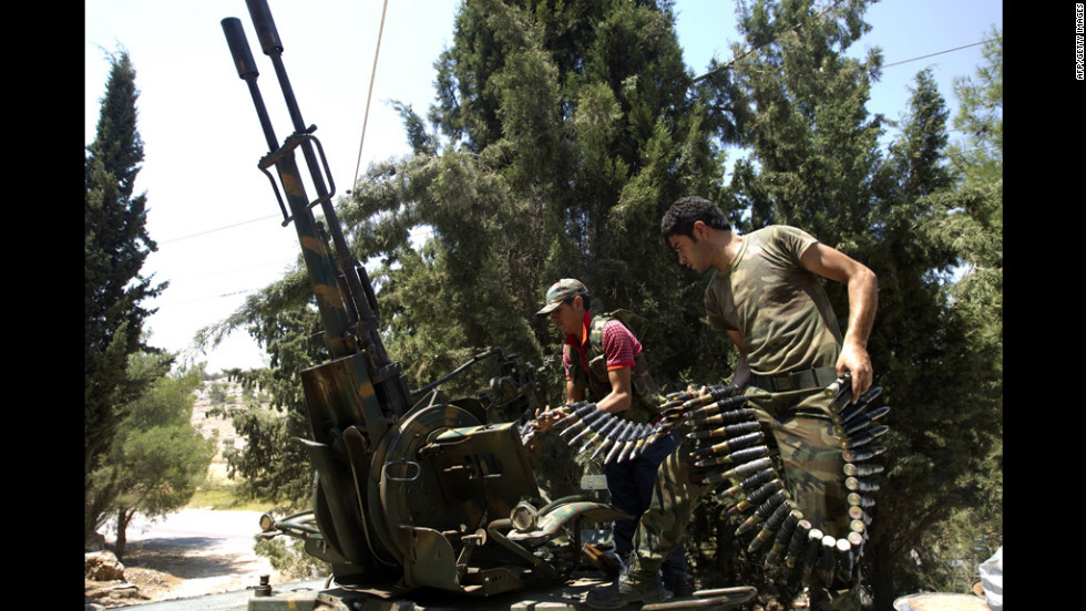 Rebel fighters load an anti-aircraft machine gun on an armored vehicle in Atareb, east of Syria's second-largest city, Aleppo, on Tuesday, July 31. Click through the gallery to view images of the fighting in July.
