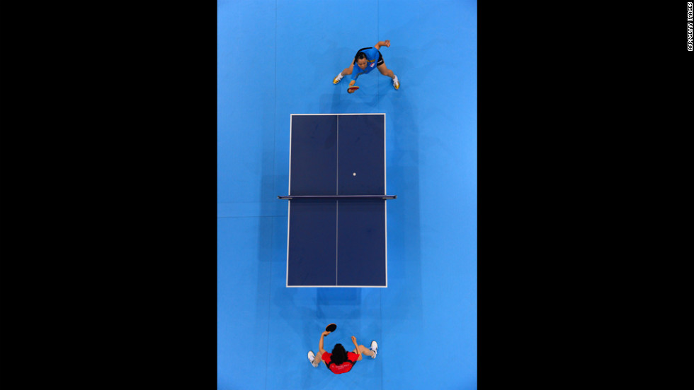 Japan's Kasumi Ishikawa, in red, faces off against Wang Yuegu of Singapore during a women's singles table-tennis match Tuesday.