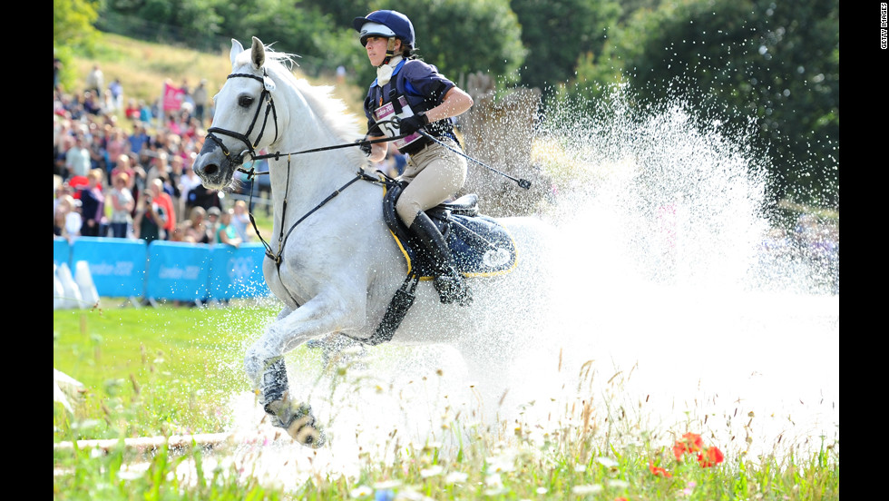 Vittoria Panizzon of Italy, riding Borough Pennyz, makes a splash in the water in the eventing cross country equestrian event.