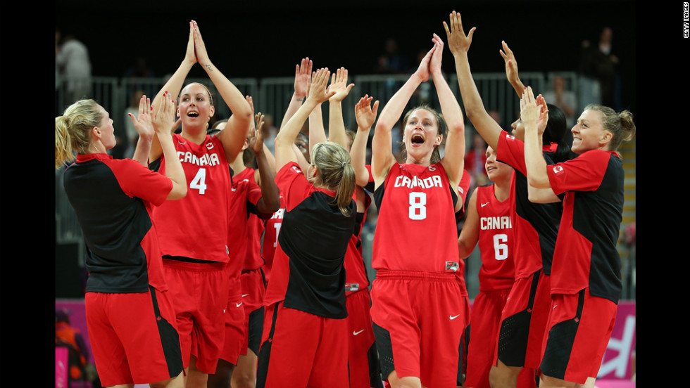 No. 4 Krista Phillips and No. 8 Kim Smith of Canada celebrate with teammates after defeating Great Britain in the women's basketball preliminary round match.