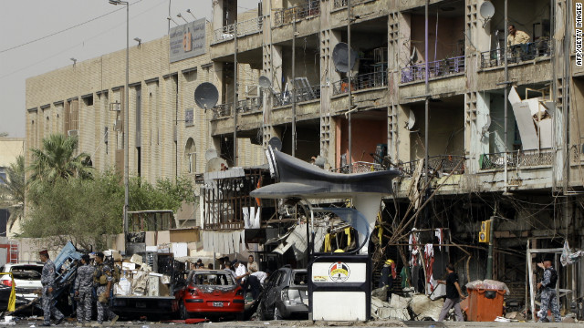 Iraqi security gather at the site of twin car bombs in the Karrada area of the capital Baghdad on July 31, 2012.