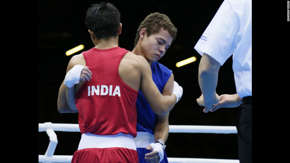 India's Devendro Singh Laishram, left, embraces Bayron Molina Figueroa of Honduras after stopping the Honduran in the first round of their light flyweight boxing match.