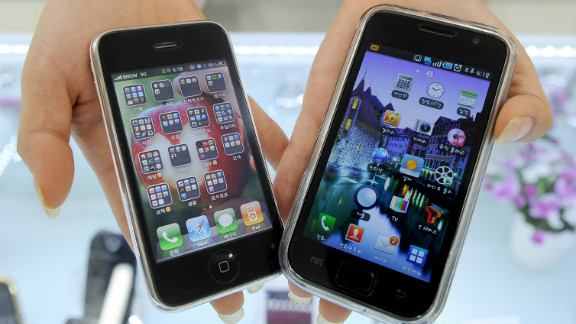 A South Korea shop manager shows Samsung Electronics' Galaxy S mobile phone, right, and Apple's iPhone 3G.