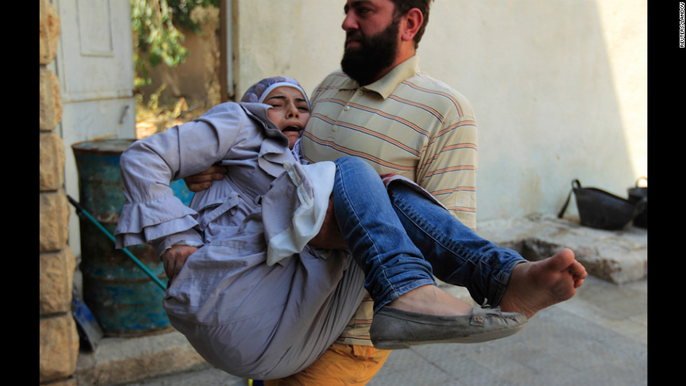 A member of the Free Syrian Army carries an injured civilian to safety in Aleppo's district of Salah Edinne on Tuesday.