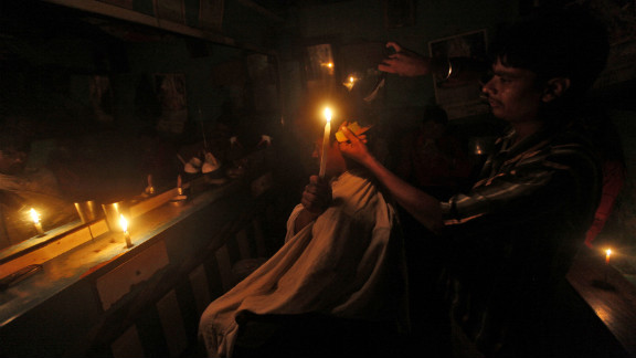 A customer holds a candle as he gets his hair cut at a barber shop in Kolkata on Tuesday.