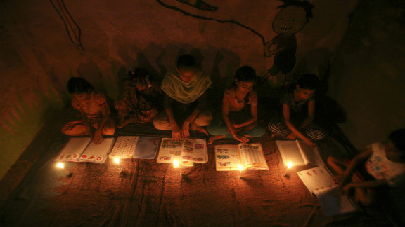Girls study by candlelight at a school in Noida on the outskirts of New Delhi during a power failure Monday, July 30.