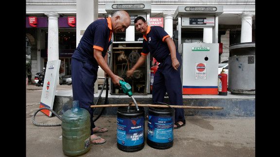 Employees manually fill containers with diesel in New Delhi on Tuesday.