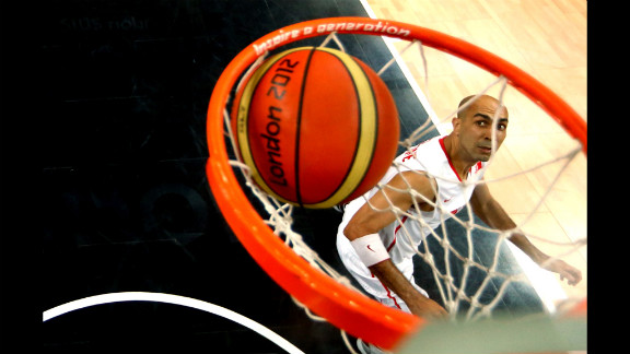 Radhouane Slimane of Tunisia watches as U.S. player Andre Iguodala's layup goes in the net during their preliminary basketball match.