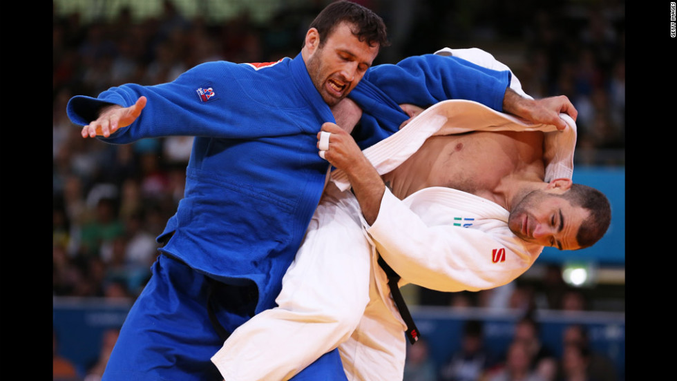 Roberto Meloni of Italy, in white, competes with Parviz Sobirov of Tajikistan during a men's under 90 kilogram Judo event.