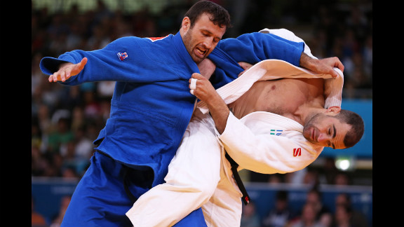 Roberto Meloni of Italy, in white, competes with Parviz Sobirov of Tajikistan during a men
