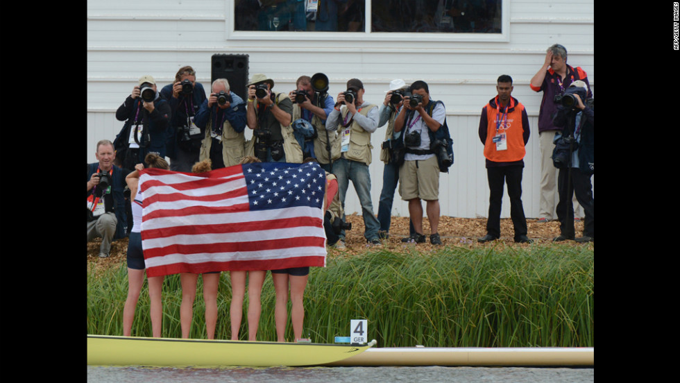 The U.S. team stands wrapped in the American flag on the podium after winning the bronze medal in the women's quadruple sculls final of the rowing event.