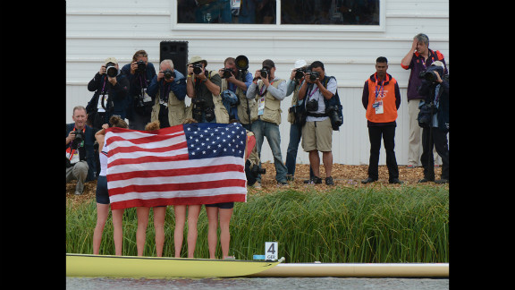 The U.S. team stands wrapped in the American flag on the podium after winning the bronze medal in the women