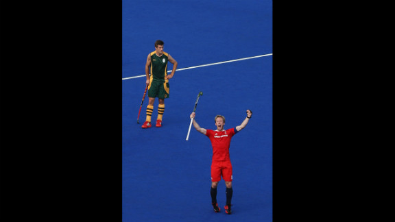 Captain Barry Middleton, in red, celebrates an equalizing goal in front of Lloyd Norris Jones of South Africa during their men