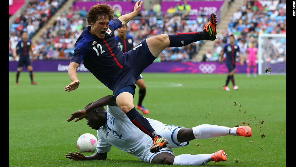Gotoku Sakai of Japan is tackled by Wilmer Crisanto of Honduras during their first-round soccer match.