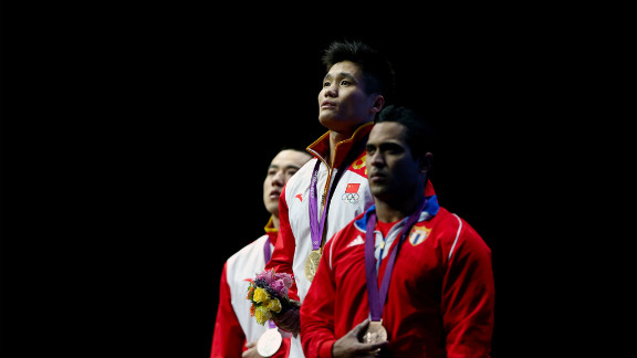 Left to right: Haojie Lu of China (silver), Xiaojun Lu of China (gold) and Ivan Cambar Rodriguez of Cuba (bronze) stand on the podium during the medal ceremony for men