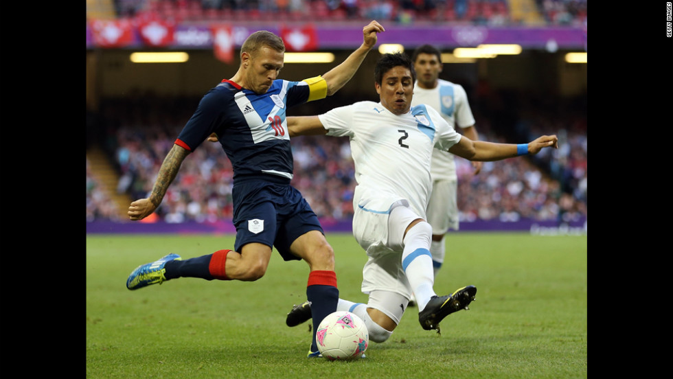 Craig Bellamy of Britain battles with Ramon Arias of Uruguay during the a men's Group A football match in Cardiff, Wales.