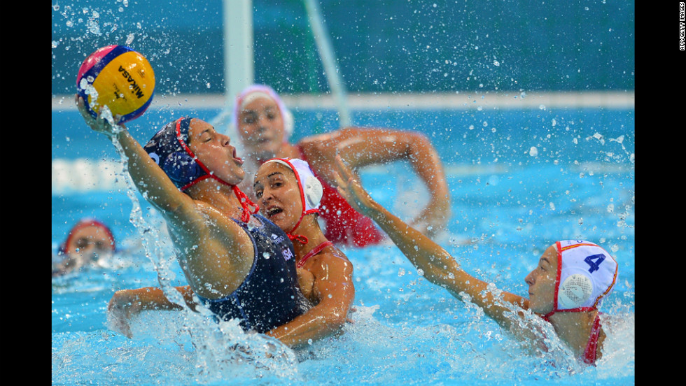 Left to right: Brenda Villa of the United States is challenged by Spain's Anni Espar Llaquet and Roser Tarrago Aymerich in a women's Group A water polo preliminary.