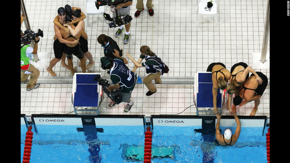 At left, Shannon Vreeland, Missy Franklin, Allison Schmitt and Dana Vollmer of the United States celebrate next to the Australian team.