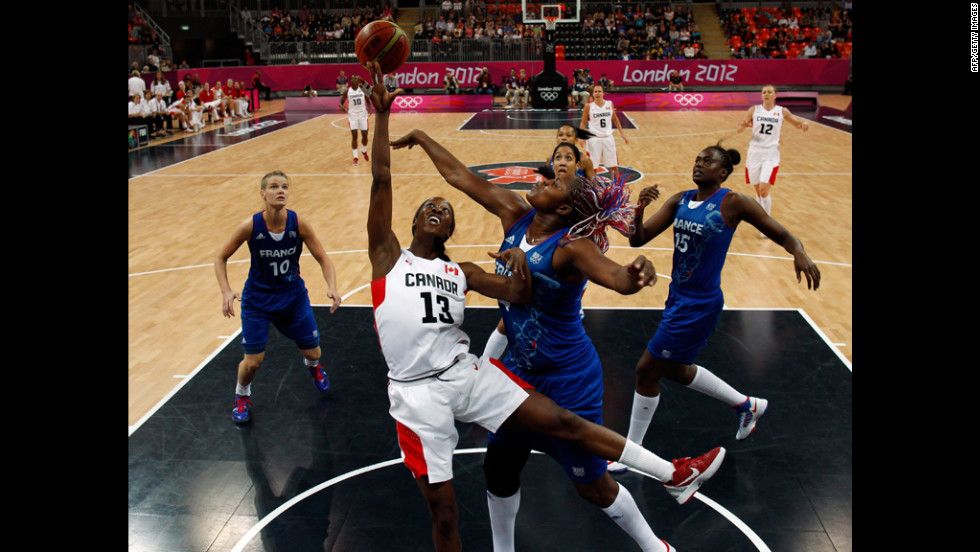 Isabelle Yacoubou of France, center, fights Tamara Tatham of Canada for the ball during a women's preliminary basketball match Wednesday.