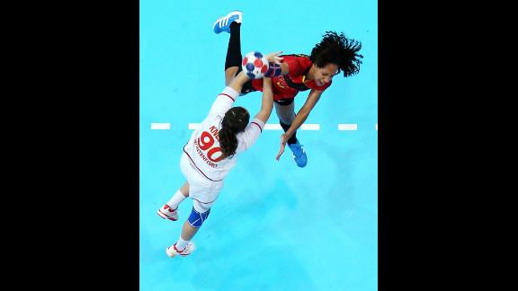 Carolina Morais of Angola throws over Milena Knezevic of Montenegro in a women