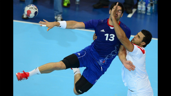 French centerback Nikola Karabatic, left, vies with a Tunisian opponent during a men