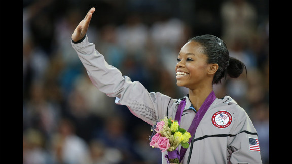 U.S. gymnast Gabrielle Douglas celebrates on the podium after winning the gymnastics women