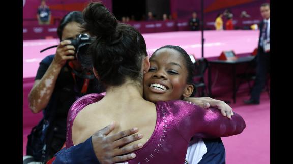 U.S. gymnast Gabby Douglas, right, embraces teammate Alexandra Raisman after winning the gymnastics women