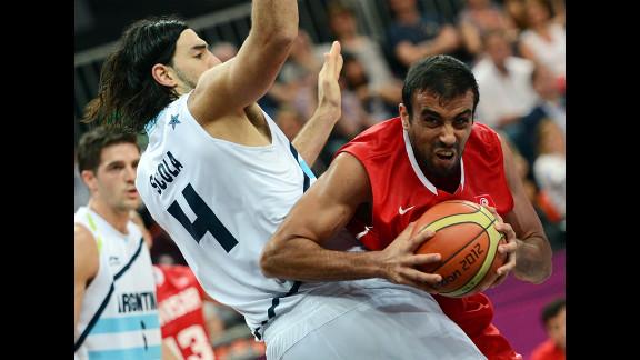 Tunisian forward Makram Ben Romdhane, right, vies with Argentine forward Luis Scola during the men