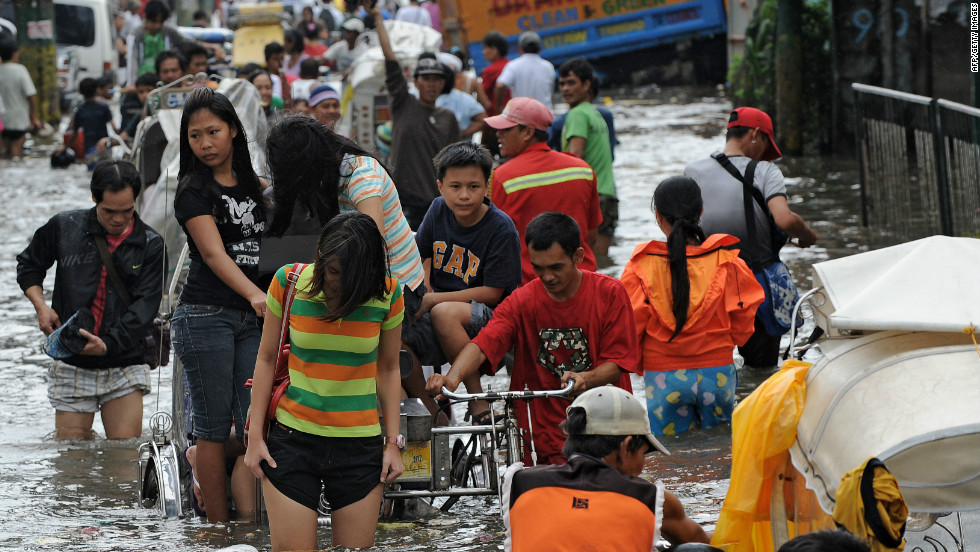 Residents wade through a flooded street in Navotas in suburban Manila. Forty-four evacuation centers have been opened due to flooding.