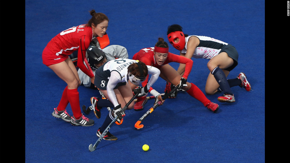 South Korea, in red, and Japan do battle during the women's field hockey match Thursday.