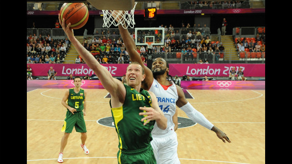 Lithuanian forward Darius Songaila, left, tries to score against French center Ronny Turiaf during a men