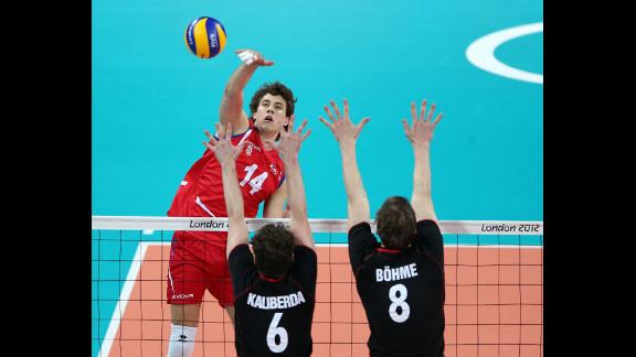 Aleksandar Atanasijevic of Serbia spikes the ball against Denys Kaliberda and Marcus Bohme of Germany.