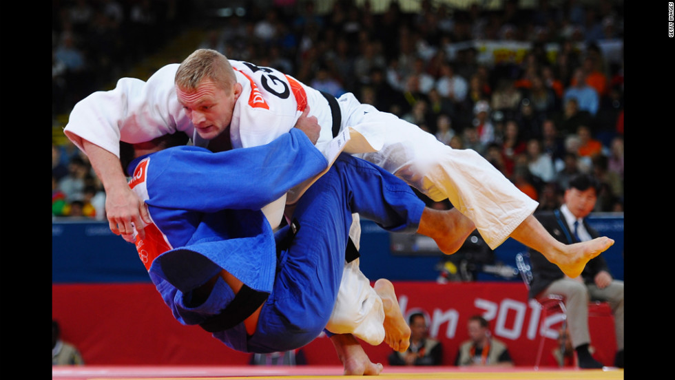 Dimitri Peters, in white, of Germany and Jevgenijs Borodavko of Latvia compete in the men's under 100-kilogram judo match.