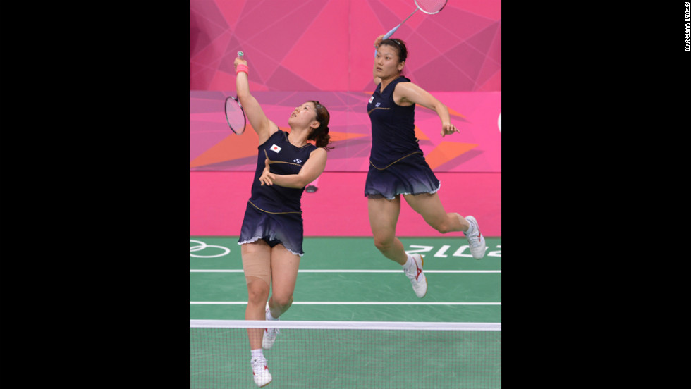 Mizuki Fujii, left, and Reika Kakiiwa, right, of Japan play a shot during their semifinal mixed doubles badminton match against Canada's Michelle Li and Alex Bruce.