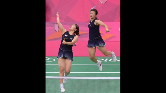 Mizuki Fujii, left, and Reika Kakiiwa, right, of Japan play a shot during their semifinal mixed doubles badminton match against Canada