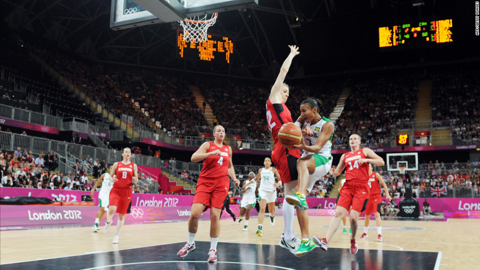 Brazilian guard Joice Rodrigues, second from right, vies with Canadian forward Lizanne Murphy during a women's preliminary round basketball match.