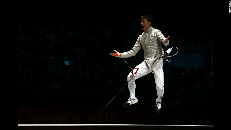 Woo Young Won of South Korea celebrates after defeating Romania to win the gold medal in the men's sabre team fencing.