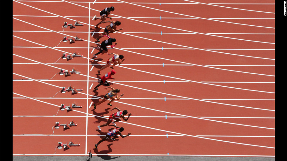 Athletes leave the blocks at the start of the women's 100-meter heat.