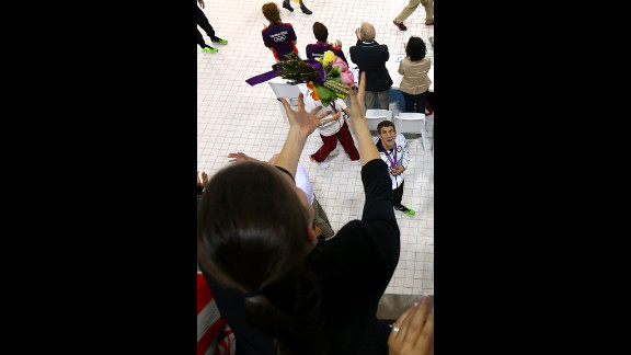 Michael Phelps throws his flowers to his sister Hilary Phelps after the medal ceremony in the men