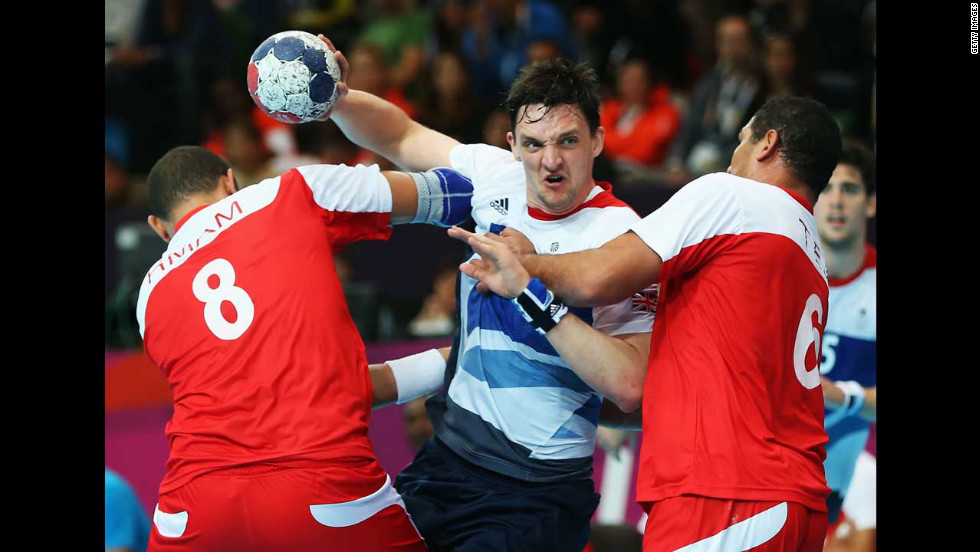 Wissem Hmam, left, and Issam Tej, right, of Tunisia defend against Christopher McDermott of Great Britain during a men's handball preliminaries match in group A.