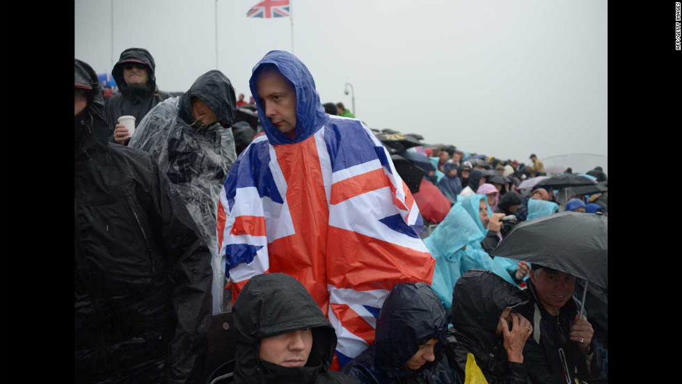 Spectators watch a rowing event as rain falls over Eton Dorney Rowing Centre west of London.