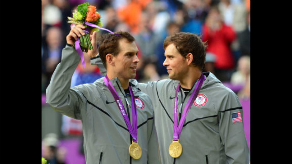 Mike Bryan, left, and Bob Bryan pose on a podium with their gold medals after winning the men