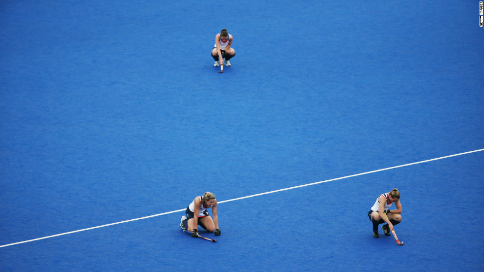 Members of Great Britain's women's hockey team slump to the ground after losing to China during a preliminary match.