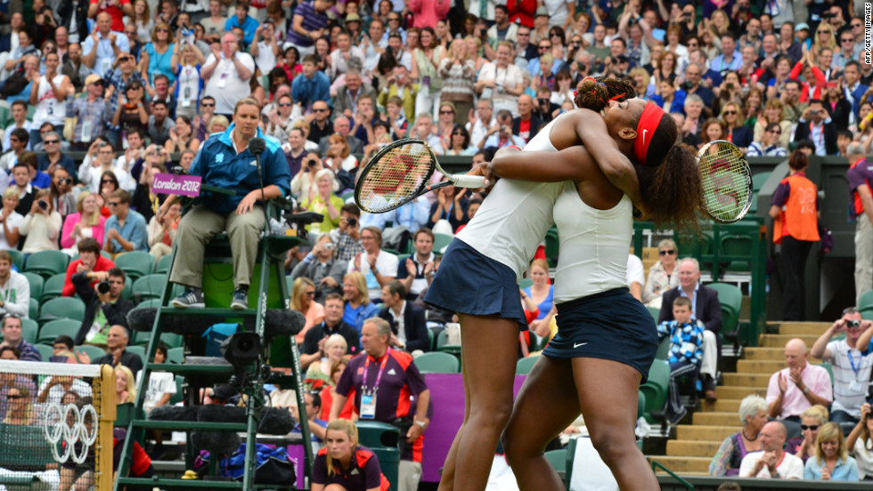 Venus Williams, left, and Serena Williams embrace after winning the women's doubles gold medal match on Sunday.