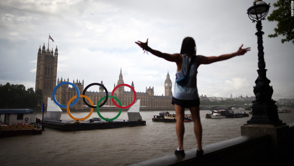 A tourist enjoys the view of giant Olympic rings floating in the River Thames opposite Parliament on Sunday, August 5, in London, England.