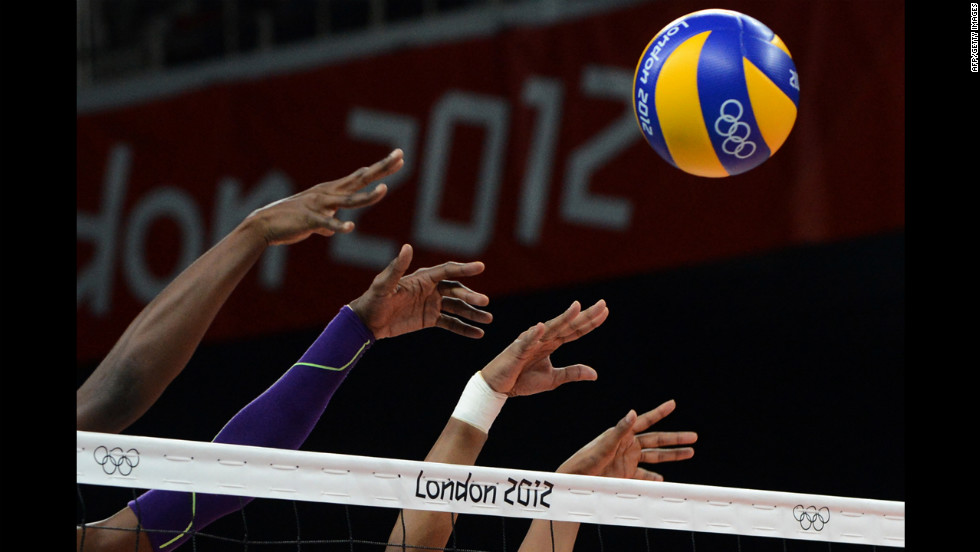 Members of the Dominican Republic women's volleyball team attempt to block a shot during a preliminary match against Algeria.