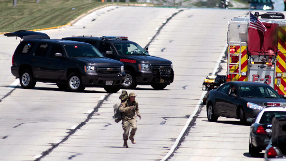 A tactical officer runs to position as SWAT officers surround the temple.