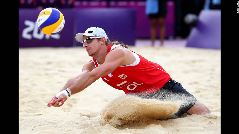 Mariusz Prudel of Poland attempts to hit a return against Emanuel Rego and Alison Cerutti of Brazil during the men's beach volleyball quarterfinal match.